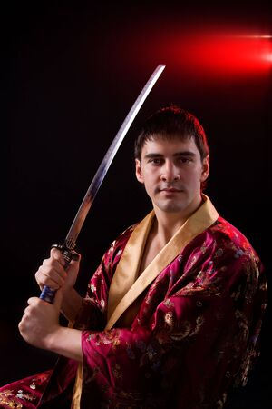 Young man holding samurai sword over dark background photo