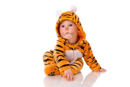 bambini pensierosi: Sei mesi bambino che indossa tuta tigre seduta isolati su bianco