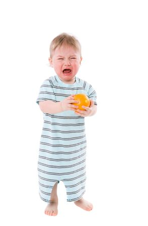 Crying baby holding orange isolated on white