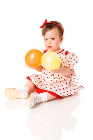 One year girl sitting holding balls isolated on white photo