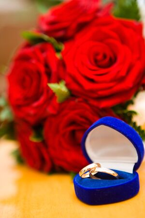 sybol: Two new Wedding rings in box with roses bouquet Stock Photo