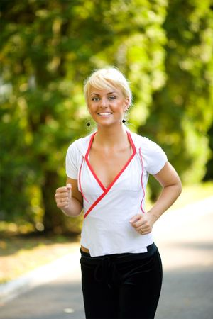 Young woman jogging in the morning summer park Stock Photo