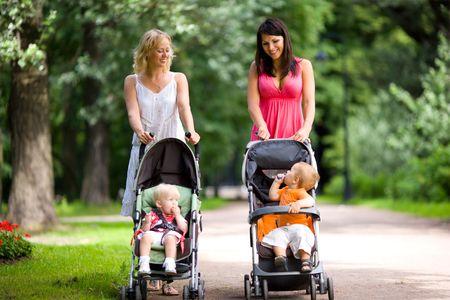ni�o empujando: Madres felices caminando juntos con los ni�os en cochecitos de ni�os