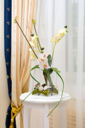 Decor made of transparent vase with white flowers  photo