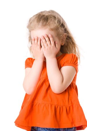 hands covering eyes: Little scared girl hiding face isolated on white