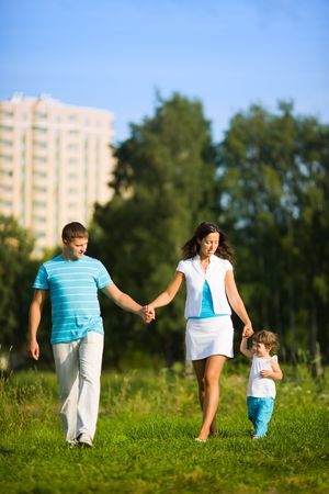 Happy Family walking in front of house outdoors  Stock Photo