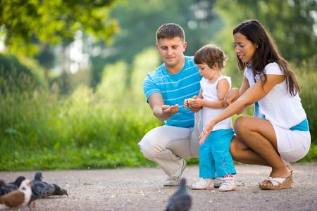 Happy Family feeding pigeons in summer park photo