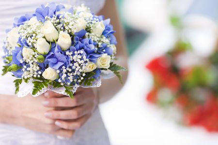 color photography: Bride holding blue and beige flowers bouquet in hands  Stock Photo