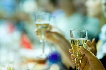 People drinking champagne in restaurant glass close up photo