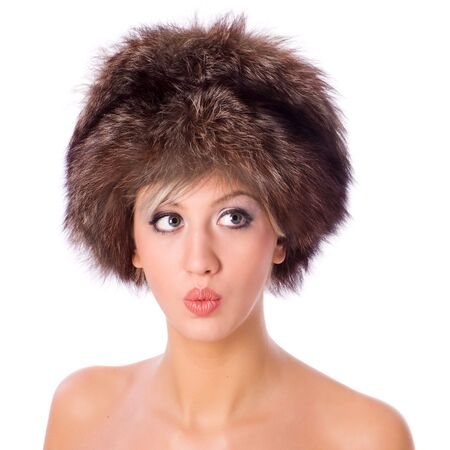 Young woman wearing fur hat making funny face isolated on white photo