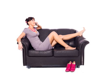 Young woman lying on couch talking on phone isolated on white photo