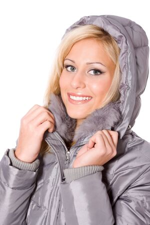 Beautiful blonde muffles up in the grey coat with hood, isolated photo