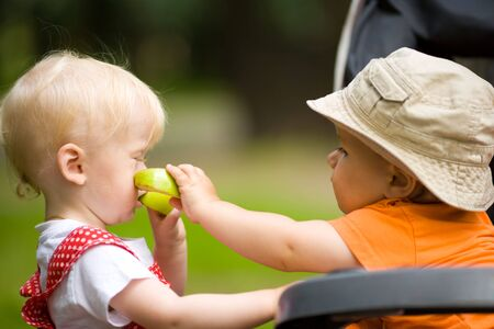 Two kids with apples outdoors looking after each other Stock Photo - 6155589