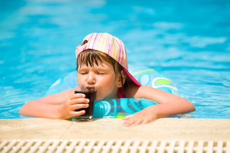 Little girl drinking soda in pool summer holidays photo