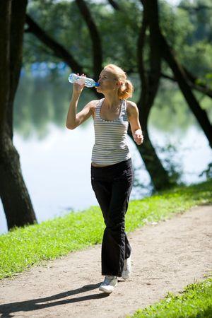 mujeres corriendo: Mujer joven agua potable V ejecuci�n aislado en blanco
