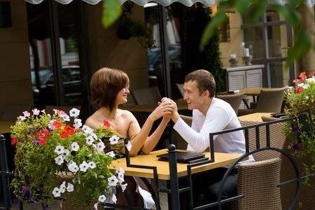 Two young lovers talking at the table Stock Photo
