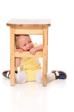 Infant hiding under chair crying isolated on white photo