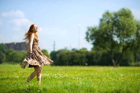 Young woman dancing happy in summer meadow photo