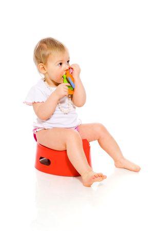 Baby girl sitting on pot isolated on white photo