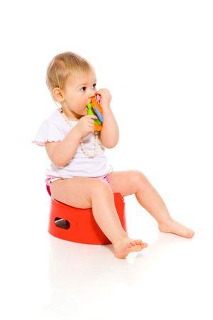potty: Baby girl sitting on pot isolated on white