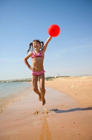 Girl jumping with balloon on the beach Stock Photo - 6952461