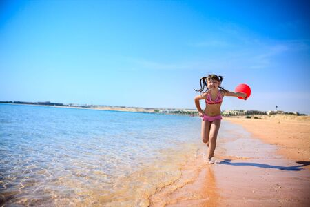 Girl Running on sunny beach with red balloon