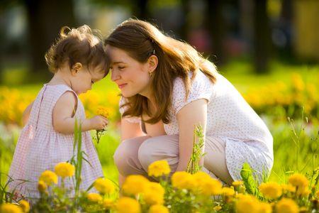 madre e hija: Feliz madre caminando con hija en parque al aire libre