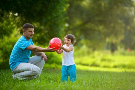 toddler girl: Happy Family playing ball outdoors summer activity