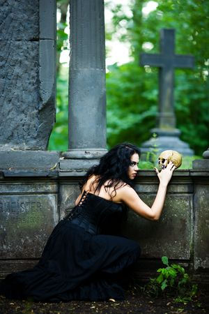 Young demonic female creature holding scull walking from crypt photo