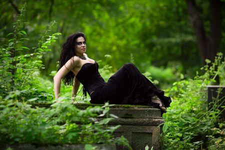 Young beautiful demonic female creature sitting on gravestone photo