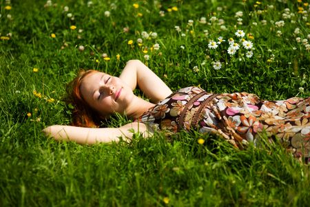 Young woman lying in grass dreaming summer day photo