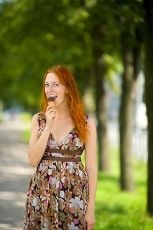 Redhead Woman eating ice-cream sunny day outdoors Banco de Imagens