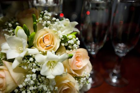 Two wedding rings on bouquet  near glasses Stock Photo - 7093280