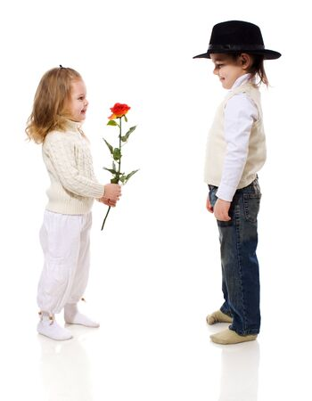 boy giving rose for his little girlfriend isolated on white Stock Photo
