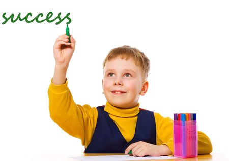 Boy writing success at table isolated on white photo