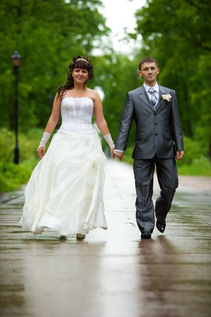 Bride and groom walking in summer park outdoors Stock Photo - 7240183
