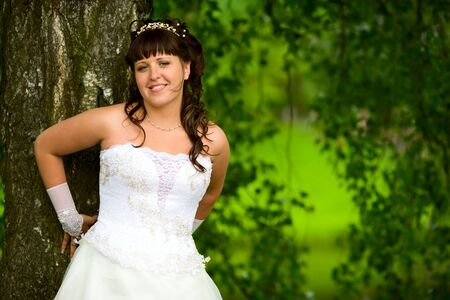 Happy Bride smiling near summer tree outdoors  photo