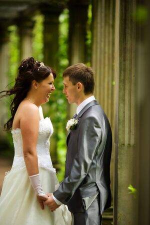 Bride and groom having fun in summer park outdoors photo