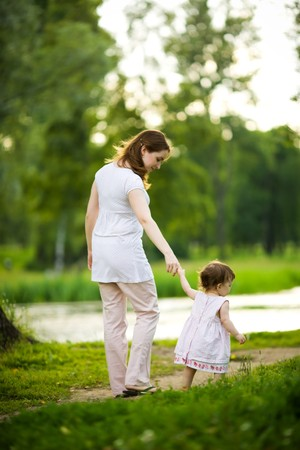 Happy mother walking with daughter in park outdoors Stock Photo