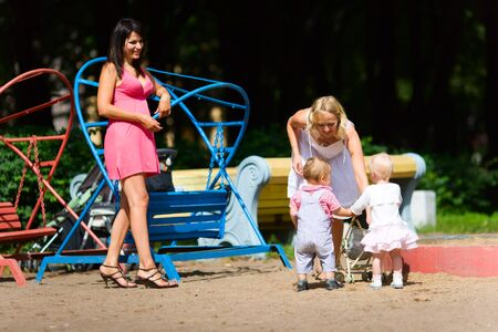 sandbox: Two Mothers playing with children on city playground