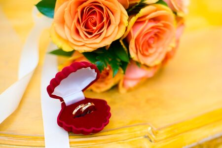 Two new Wedding rings in box with roses bouquet Stock Photo