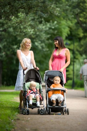 poussette: M�res heureuse marche avec les enfants dans les poussettes