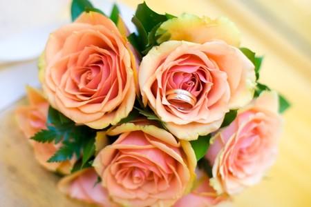 Two Golden Wedding Rings on roses macro shot Stock Photo - 7344424
