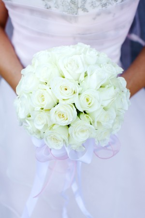 Bride holding roses vivid flowers bouquet in hands