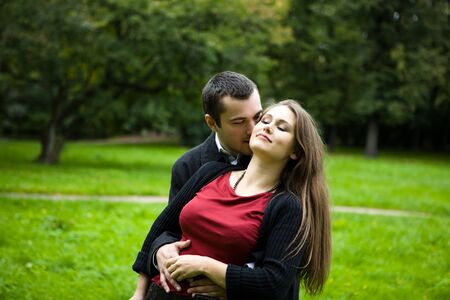 Two young lovers enjoying each other in park photo