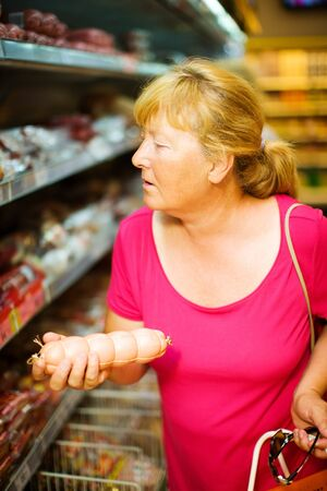 Mature Housewife buying sausage in supermarket photo
