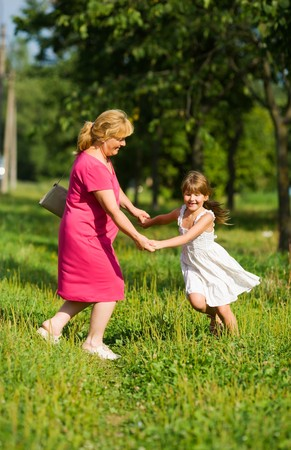 Grandmother with child dancing together outdoors photo