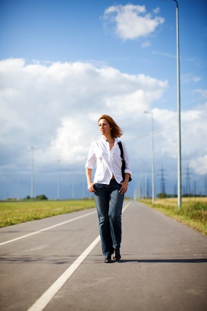 one young woman only: Serious woman walking empty road summer day