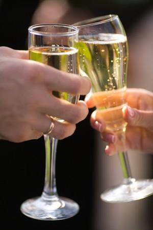 brindisi champagne: Due Champagne nelle mani della nuova coppia sposata closeup