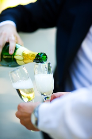Two men pouring Champagne outdoors hands closeup photo